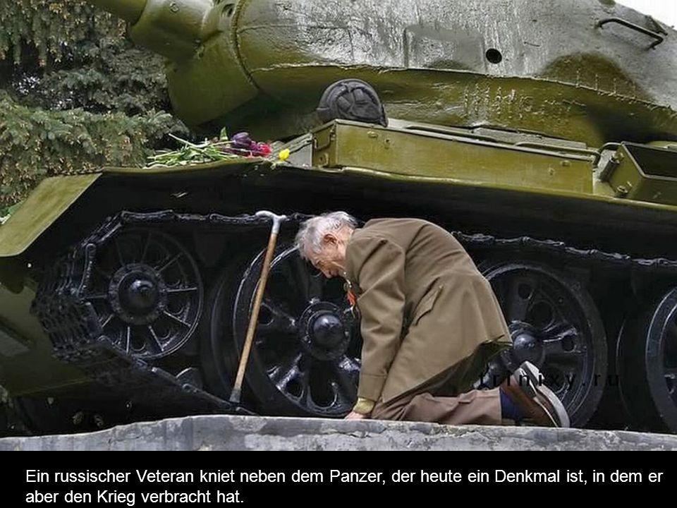 Ein russischer Veteran kniet neben dem Panzer, der heute ein Denkmal ist, in dem er aber den Krieg verbracht hat.