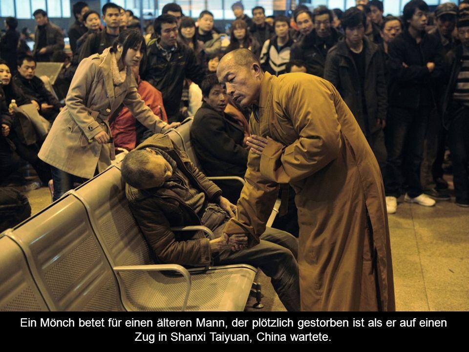 Ein Mönch betet für einen älteren Mann, der plötzlich gestorben ist als er auf einen Zug in Shanxi Taiyuan, China wartete.