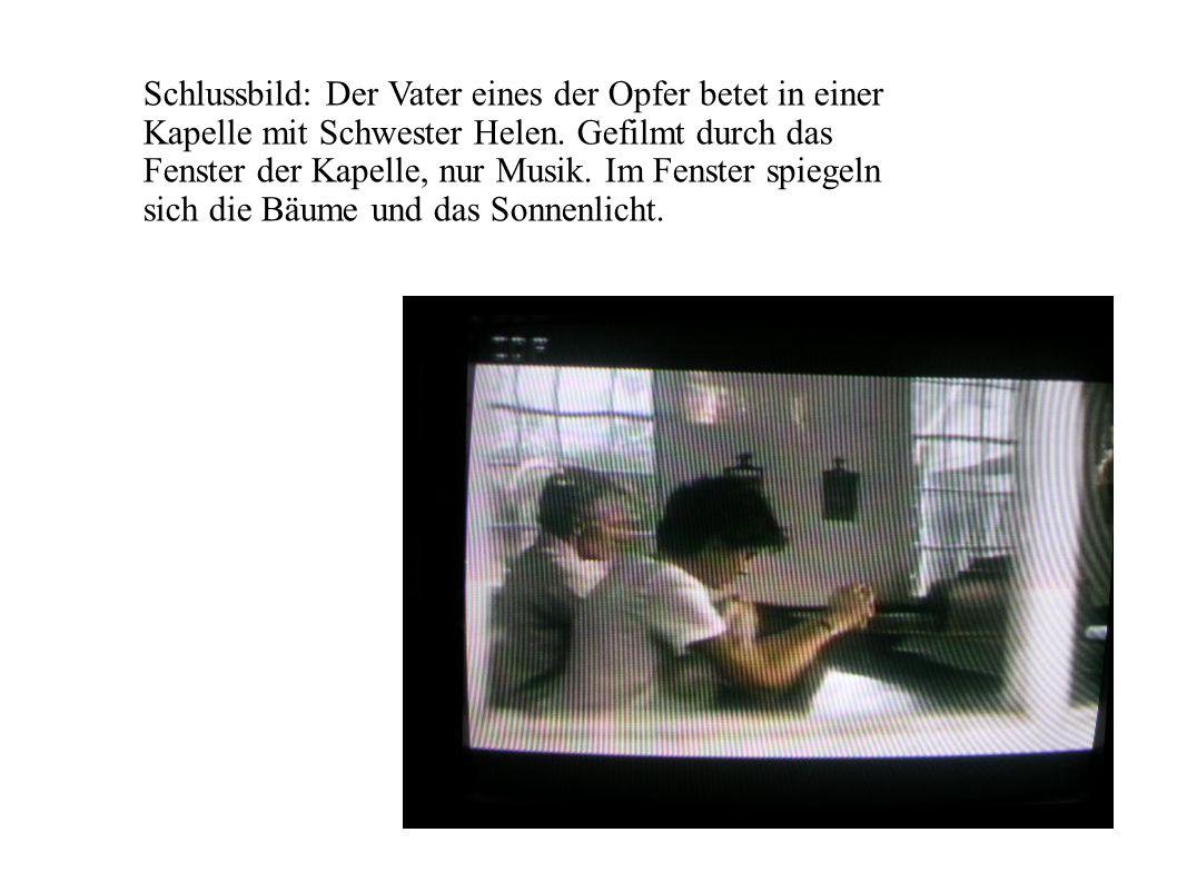 Schlussbild: Der Vater eines der Opfer betet in einer Kapelle mit Schwester Helen. Gefilmt durch das Fenster der Kapelle, nur Musik. Im Fenster spiege