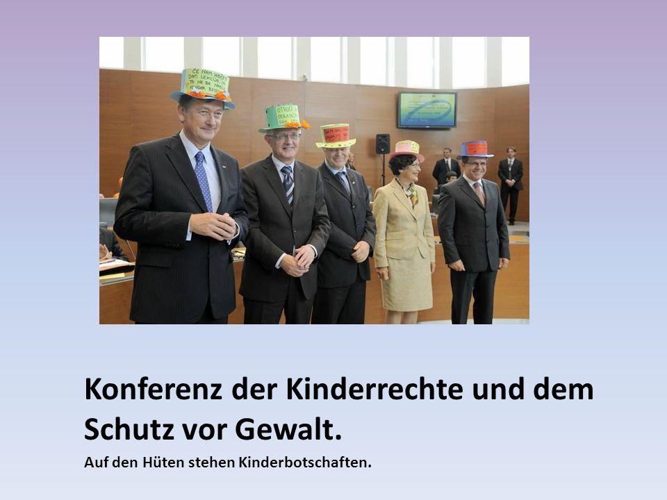 Konferenz der Kinderrechte und dem Schutz vor Gewalt. Auf den Hüten stehen Kinderbotschaften.