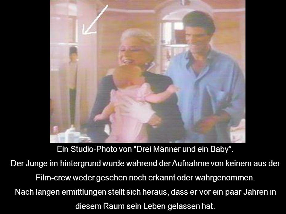 Ein Studio-Photo von Drei Männer und ein Baby. Der Junge im hintergrund wurde während der Aufnahme von keinem aus der Film-crew weder gesehen noch erk
