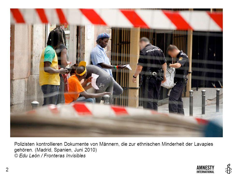 2 Polizisten kontrollieren Dokumente von Männern, die zur ethnischen Minderheit der Lavapies gehören.