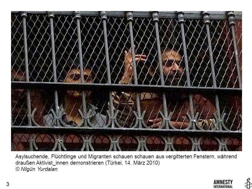 3 Asylsuchende, Flüchtlinge und Migranten schauen schauen aus vergitterten Fenstern, während draußen Aktivist_innen demonstrieren (Türkei, 14.