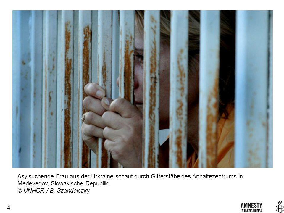 4 Asylsuchende Frau aus der Urkraine schaut durch Gitterstäbe des Anhaltezentrums in Medevedov, Slowakische Republik.