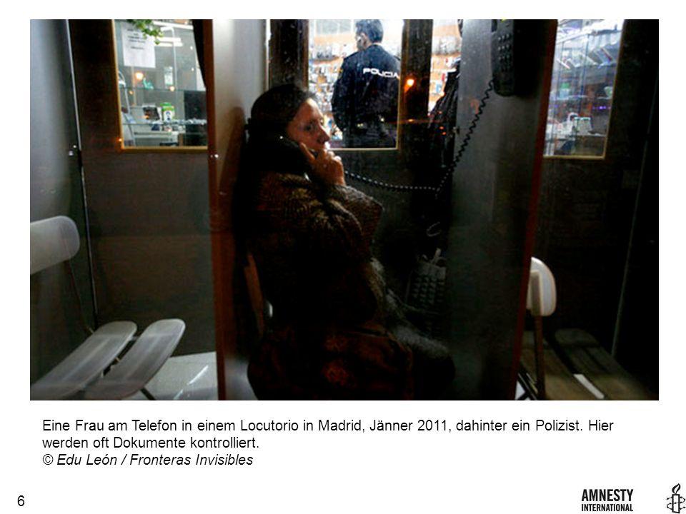 6 Eine Frau am Telefon in einem Locutorio in Madrid, Jänner 2011, dahinter ein Polizist.