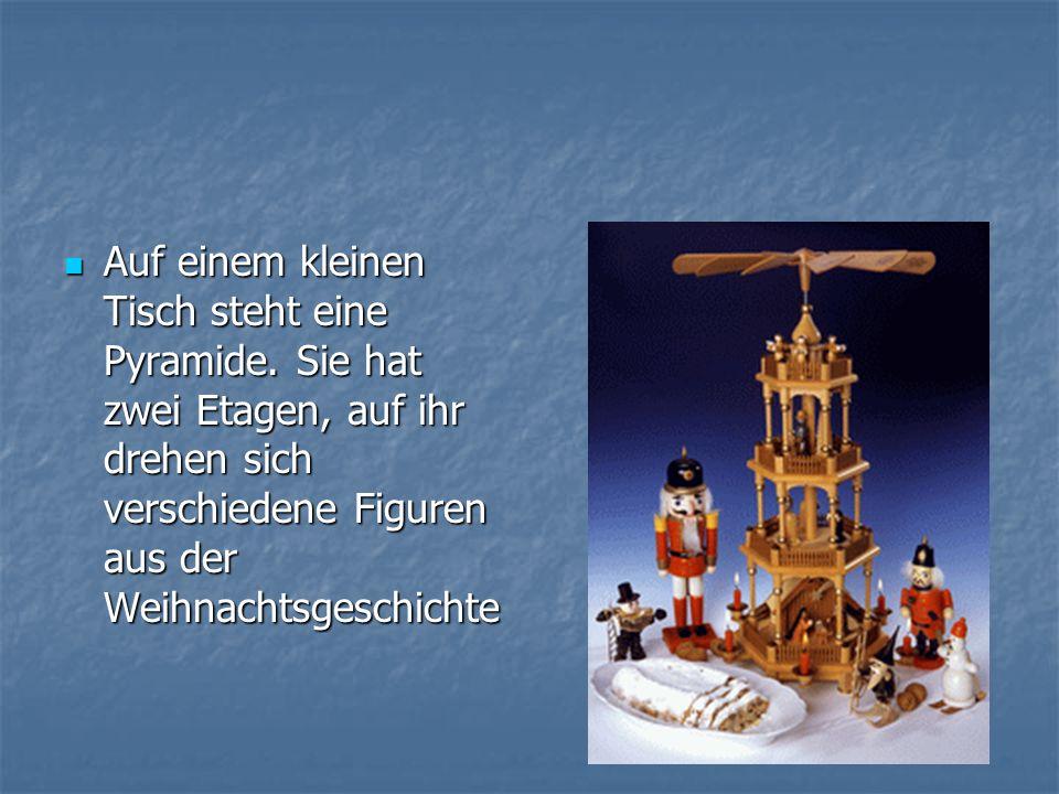 Auf einem kleinen Tisch steht eine Pyramide. Sie hat zwei Etagen, auf ihr drehen sich verschiedene Figuren aus der Weihnachtsgeschichte Auf einem klei