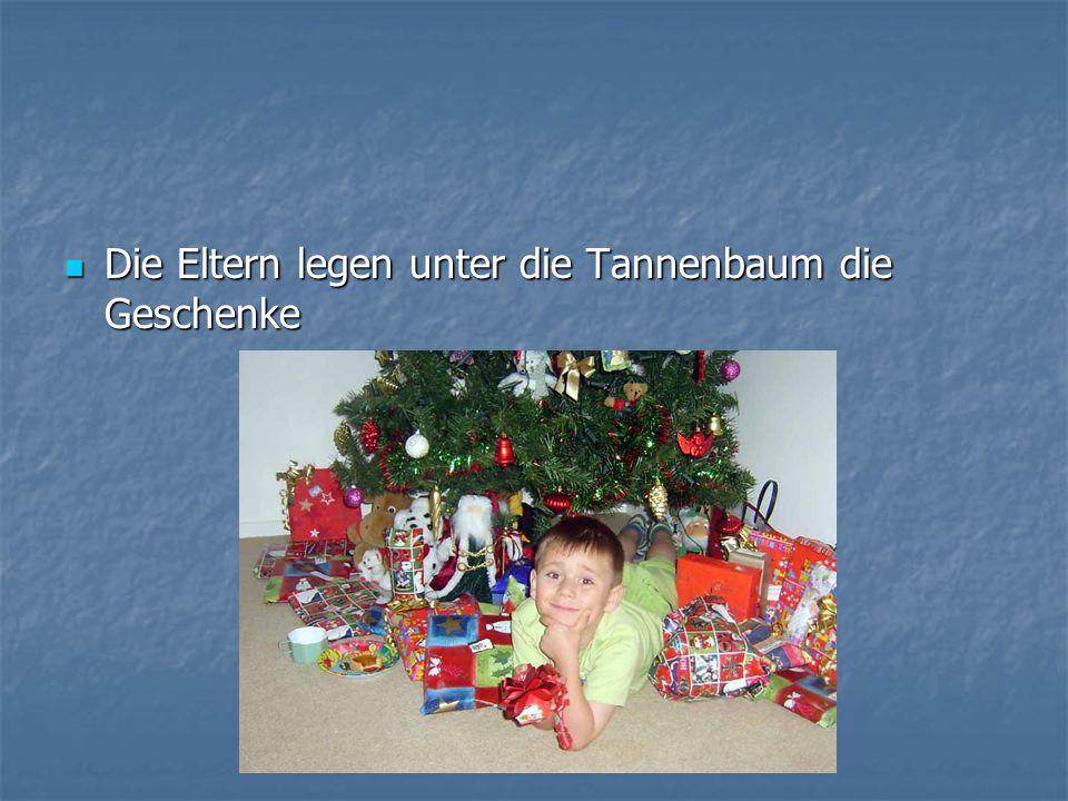 Die Eltern legen unter die Tannenbaum die Geschenke Die Eltern legen unter die Tannenbaum die Geschenke