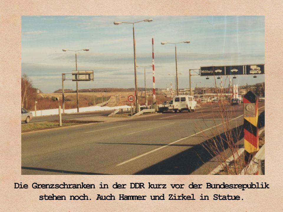 Die Grenzschranken in der DDR kurz vor der Bundesrepublik stehen noch. Auch Hammer und Zirkel in Statue.