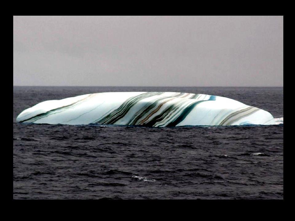 Das Erstaunen von gestreiften Eisbergen, das Icebergs im Antarktischen Gebiet manchmal Streifen hat, bildete neben Schichten von Schnee, der zu andere