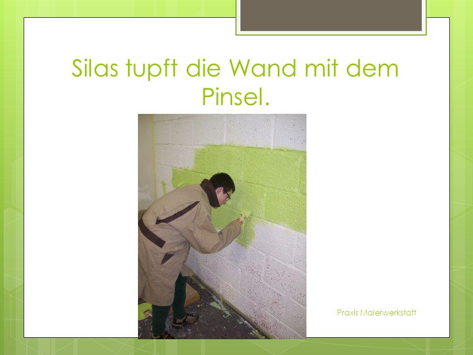 Silas tupft die Wand mit dem Pinsel. Praxis Malerwerkstatt