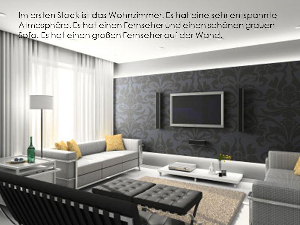 Im ersten Stock ist das Wohnzimmer. Es hat eine sehr entspannte Atmosphäre. Es hat einen Fernseher und einen schönen grauen Sofa. Es hat einen großen