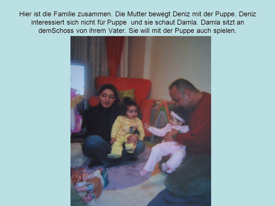 Hier ist die Familie zusammen. Die Mutter bewegt Deniz mit der Puppe.
