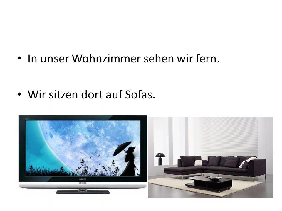In unser Wohnzimmer sehen wir fern. Wir sitzen dort auf Sofas.