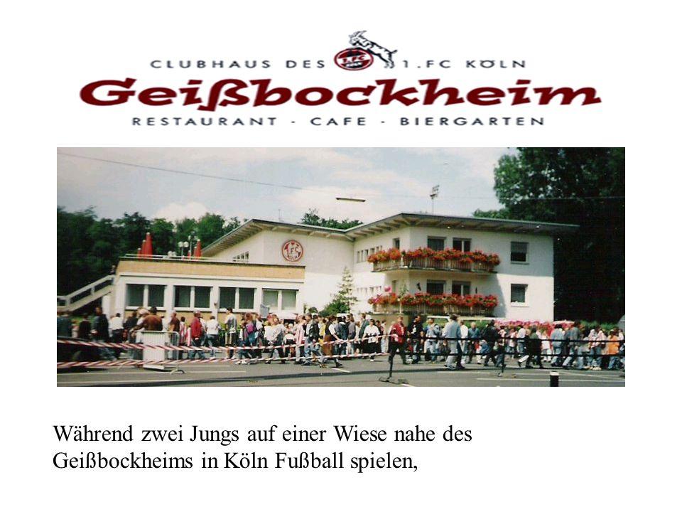 Während zwei Jungs auf einer Wiese nahe des Geißbockheims in Köln Fußball spielen,