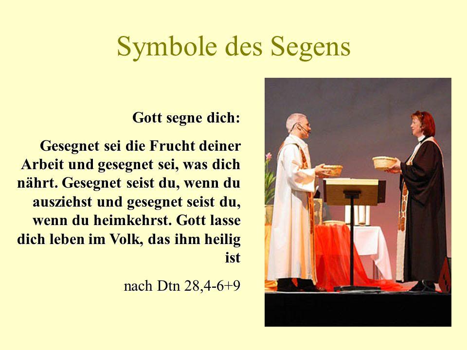 Symbole des Segens Liturgen nehmen jeweils eine Spruchschale vom Altar und halten sie hoch