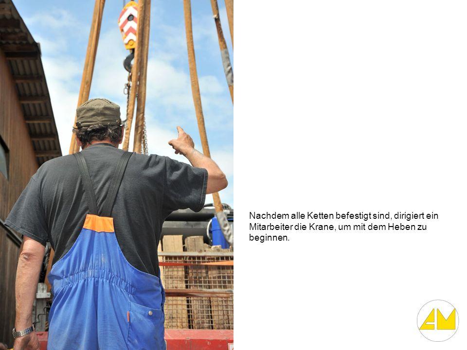 Nachdem alle Ketten befestigt sind, dirigiert ein Mitarbeiter die Krane, um mit dem Heben zu beginnen.