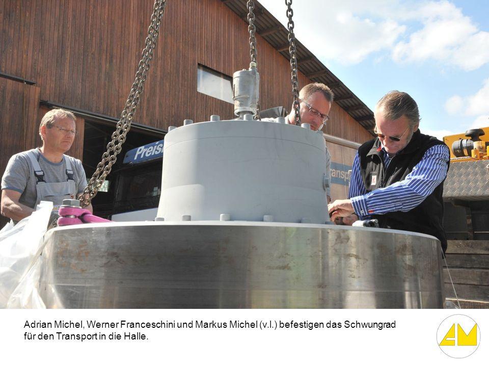 Adrian Michel, Werner Franceschini und Markus Michel (v.l.) befestigen das Schwungrad für den Transport in die Halle.