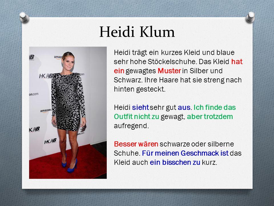 Heidi Klum Heidi trägt ein kurzes Kleid und blaue sehr hohe Stöckelschuhe. Das Kleid hat ein gewagtes Muster in Silber und Schwarz. Ihre Haare hat sie