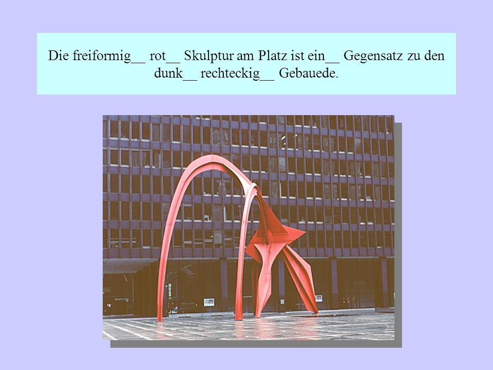 Die freiformig__ rot__ Skulptur am Platz ist ein__ Gegensatz zu den dunk__ rechteckig__ Gebauede.
