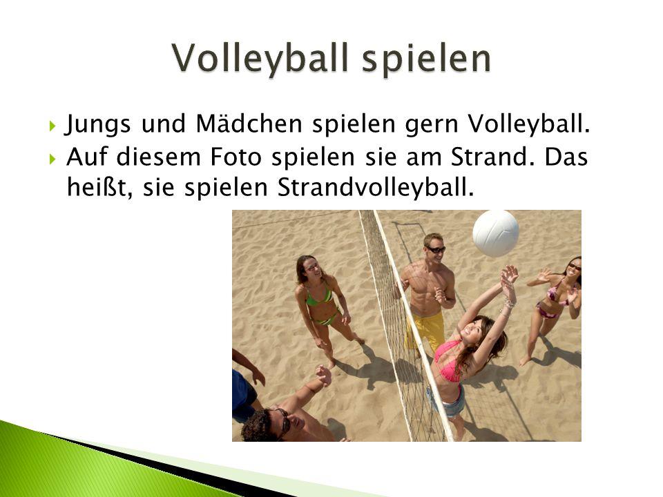  Jungs und Mädchen spielen gern Volleyball. Auf diesem Foto spielen sie am Strand.