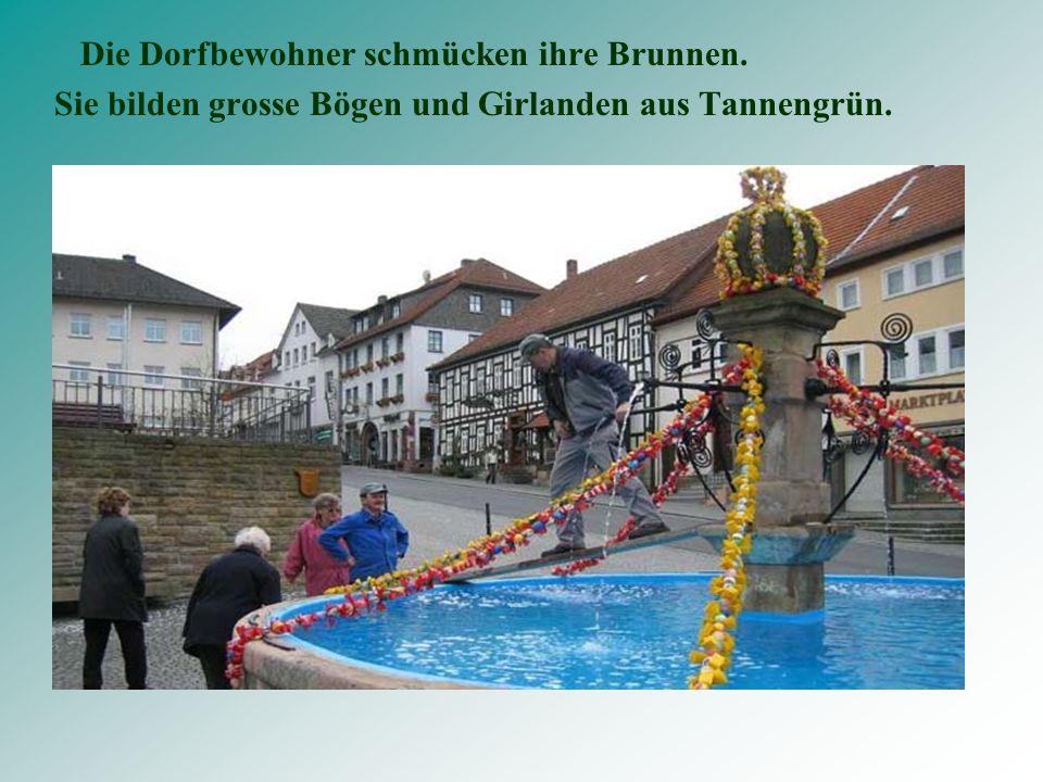 Die Dorfbewohner schmücken ihre Brunnen. Sie bilden grosse Bögen und Girlanden aus Tannengrün.