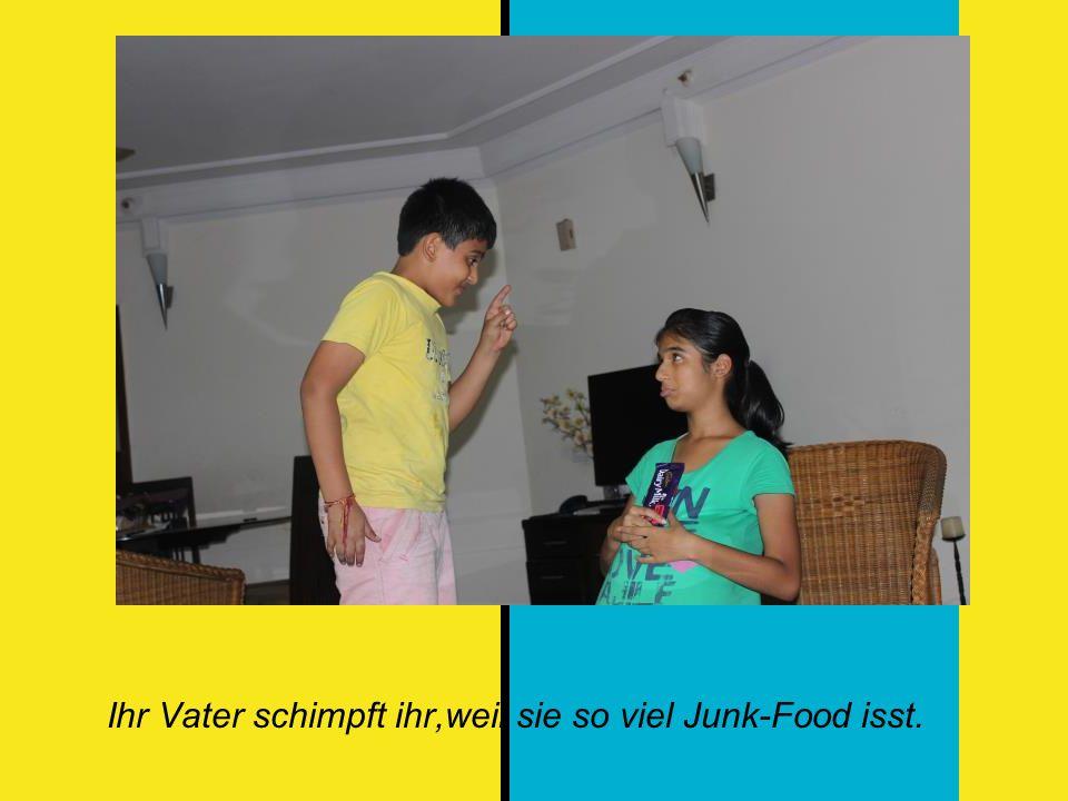 Ihr Vater schimpft ihr,weil sie so viel Junk-Food isst.