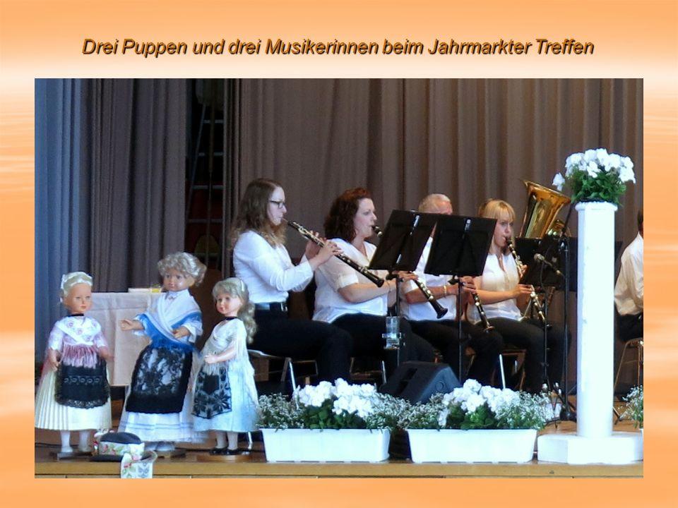 Drei Puppen und drei Musikerinnen beim Jahrmarkter Treffen