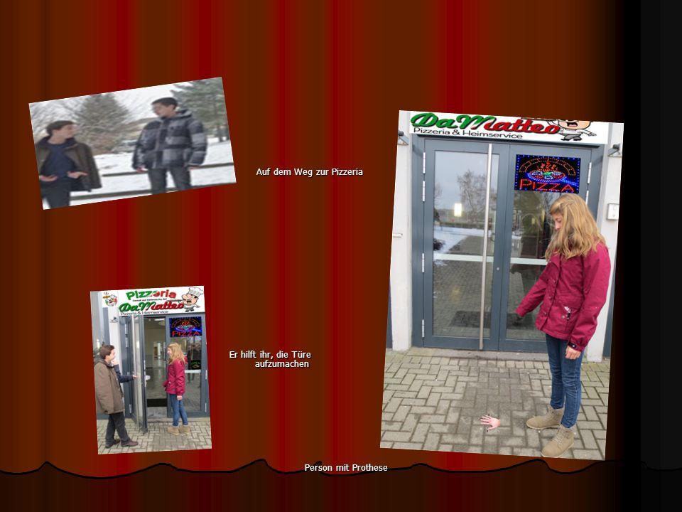 Auf dem Weg zur Pizzeria Person mit Prothese Er hilft ihr, die Türe aufzumachen