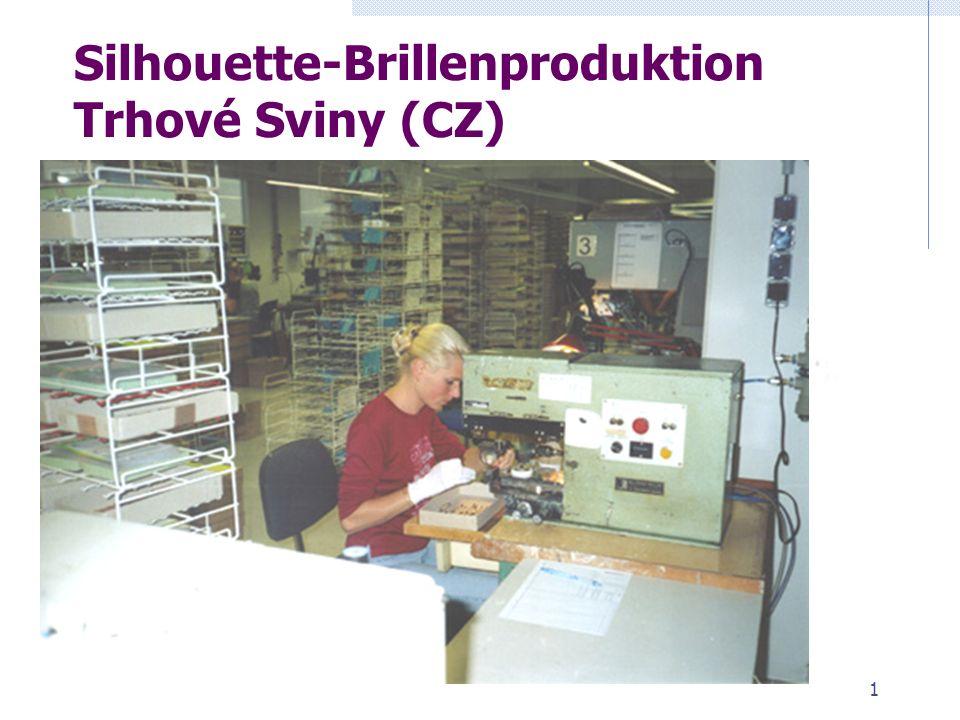1 Eine Person stempelt mit einem Automaten per Knopfdruck ein farbiges Logo auf einen Brillenbügel.