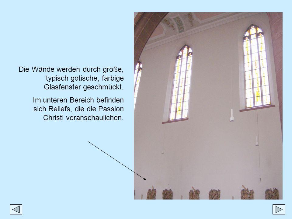 Die Wände werden durch große, typisch gotische, farbige Glasfenster geschmückt. Im unteren Bereich befinden sich Reliefs, die die Passion Christi vera