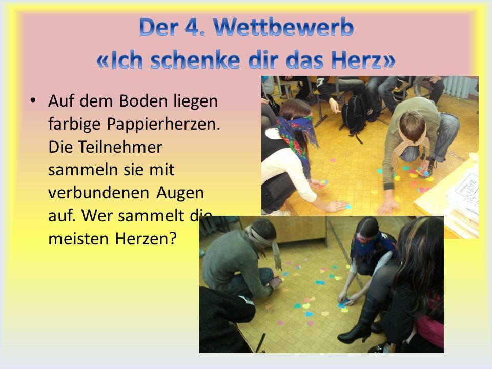 Auf dem Boden liegen farbige Pappierherzen. Die Teilnehmer sammeln sie mit verbundenen Augen auf.