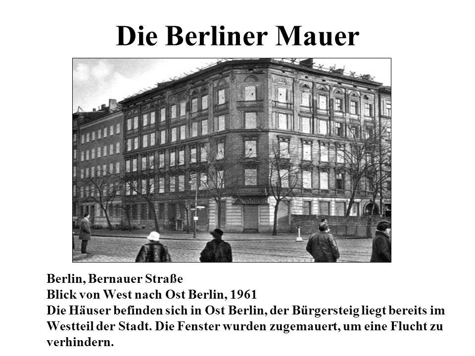 Die Berliner Mauer Berlin, Bernauer Straße Blick von West nach Ost Berlin, 1961 Die Häuser befinden sich in Ost Berlin, der Bürgersteig liegt bereits