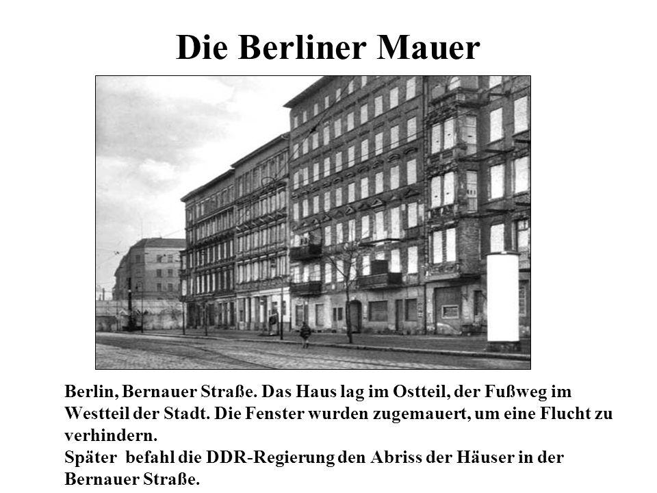Die Berliner Mauer Berlin, Bernauer Straße. Das Haus lag im Ostteil, der Fußweg im Westteil der Stadt. Die Fenster wurden zugemauert, um eine Flucht z