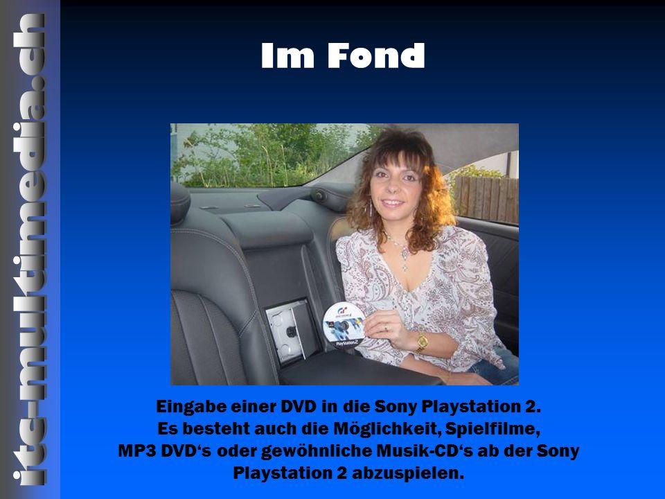 Im Fond Eingabe einer DVD in die Sony Playstation 2. Es besteht auch die Möglichkeit, Spielfilme, MP3 DVDs oder gewöhnliche Musik-CDs ab der Sony Play