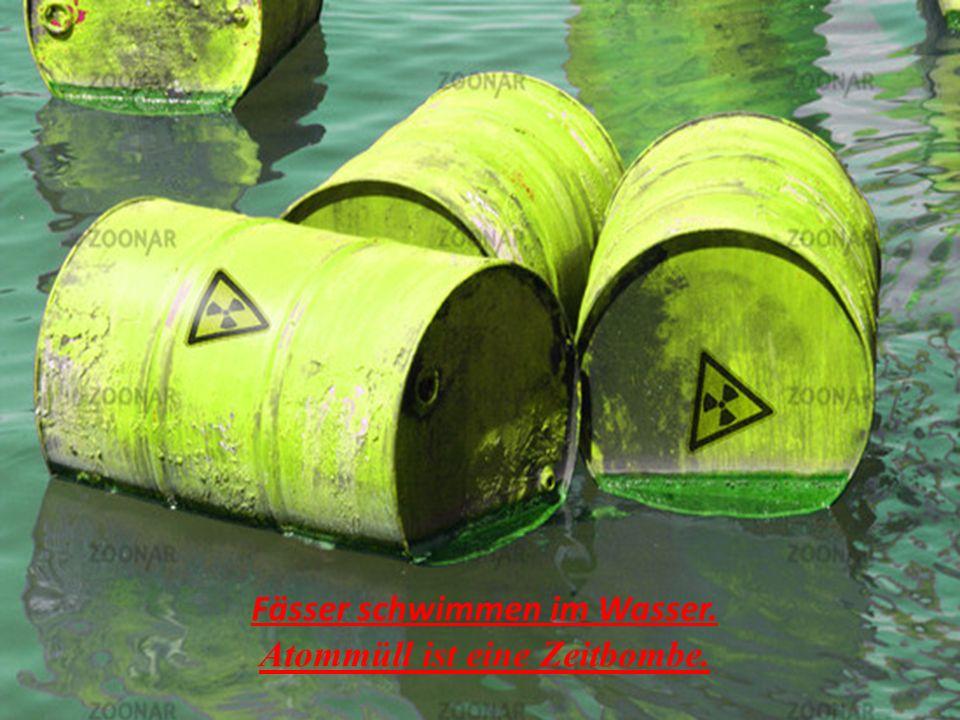 Fässer schwimmen im Wasser. Atommüll ist eine Zeitbombe.