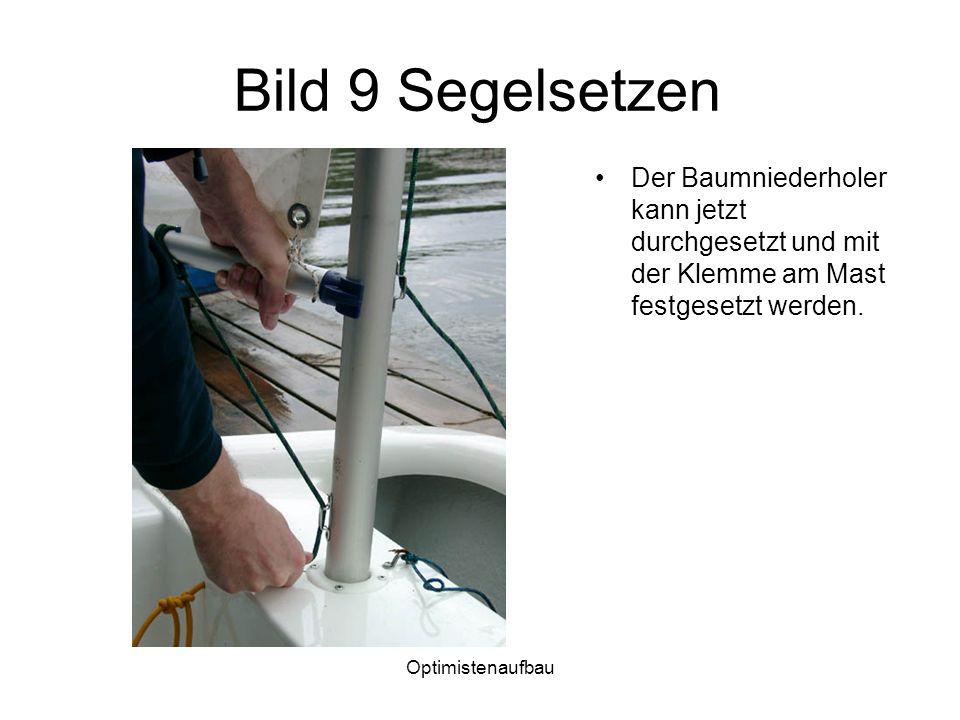 Optimistenaufbau Bild 9 Segelsetzen Der Baumniederholer kann jetzt durchgesetzt und mit der Klemme am Mast festgesetzt werden.
