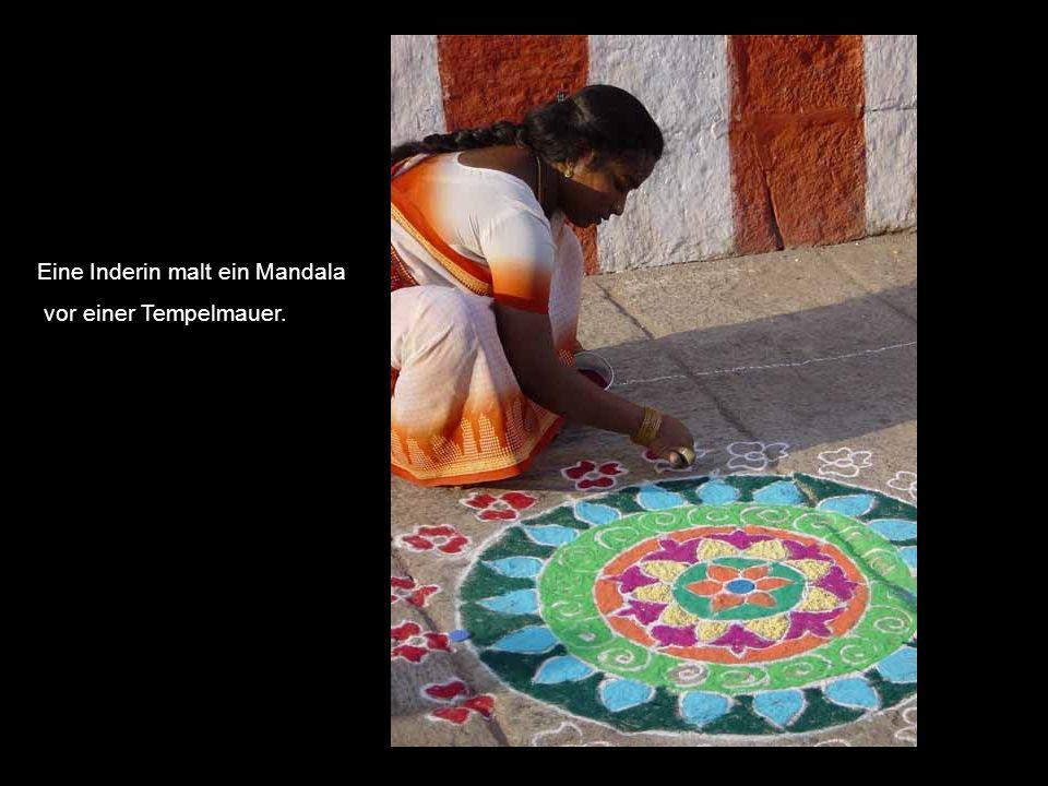 Eine Inderin malt ein Mandala vor einer Tempelmauer.