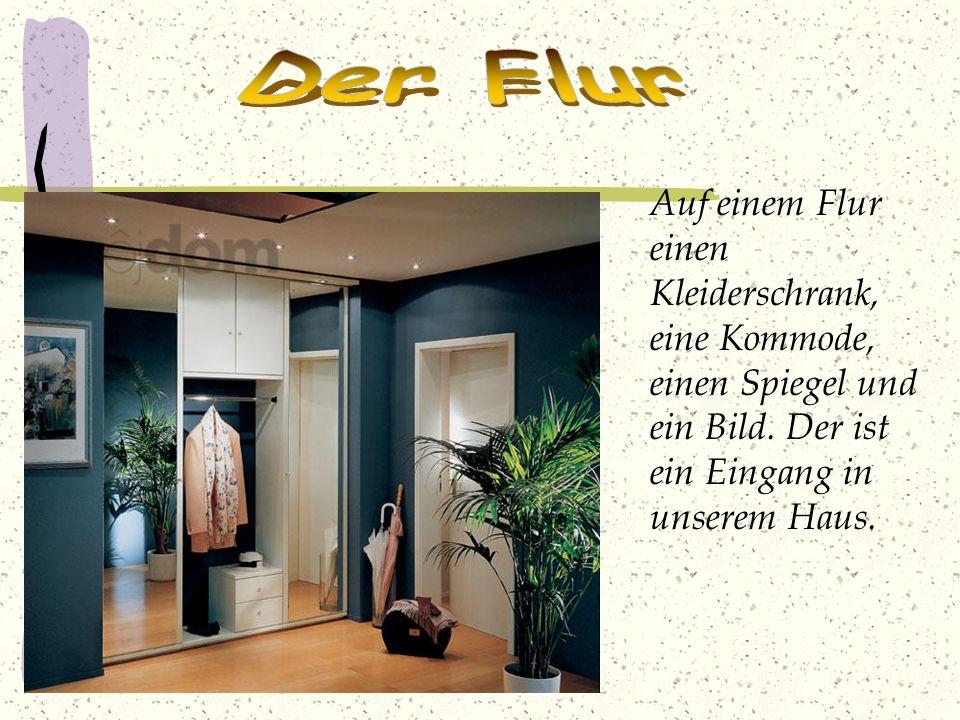 Auf einem Flur einen Kleiderschrank, eine Kommode, einen Spiegel und ein Bild. Der ist ein Eingang in unserem Haus.