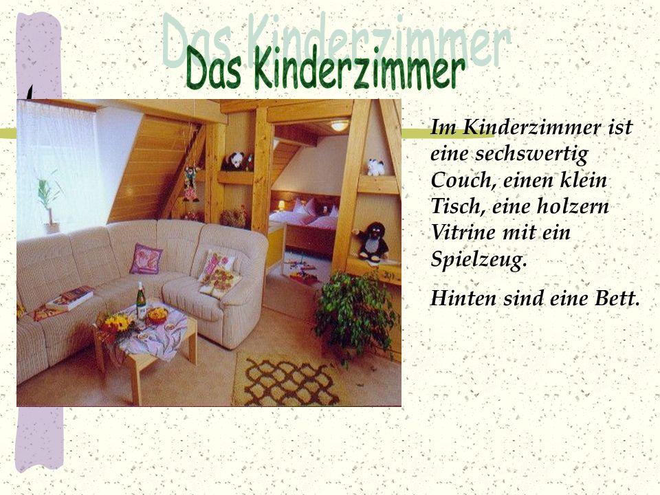 Im Kinderzimmer ist eine sechswertig Couch, einen klein Tisch, eine holzern Vitrine mit ein Spielzeug. Hinten sind eine Bett.