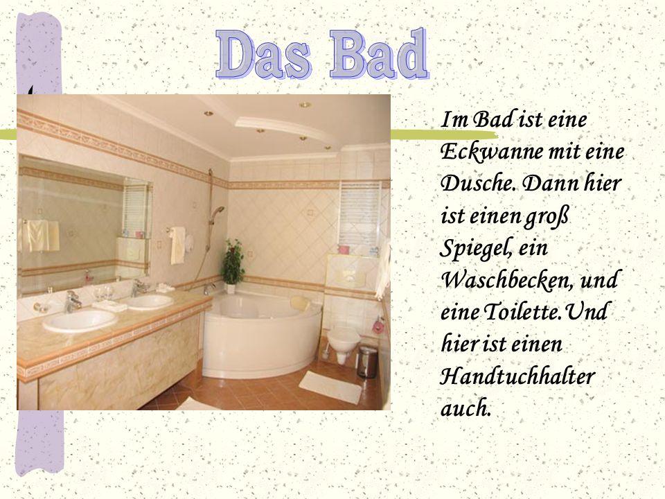 Im Bad ist eine Eckwanne mit eine Dusche. Dann hier ist einen groß Spiegel, ein Waschbecken, und eine Toilette.Und hier ist einen Handtuchhalter auch.