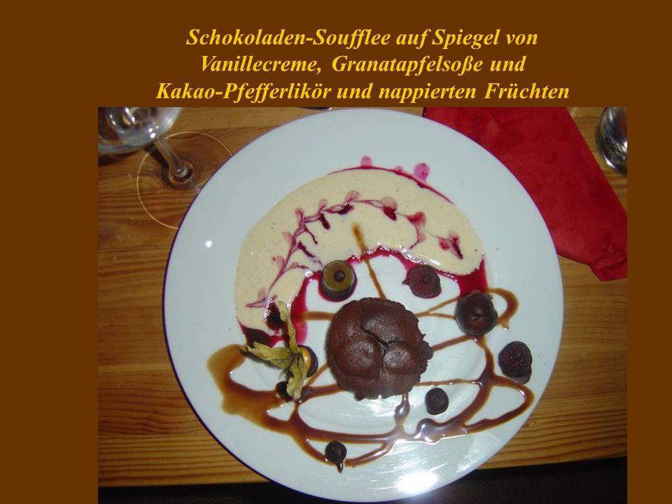 Schokoladen-Soufflee auf Spiegel von Vanillecreme, Granatapfelsoße und Kakao-Pfefferlikör und nappierten Früchten
