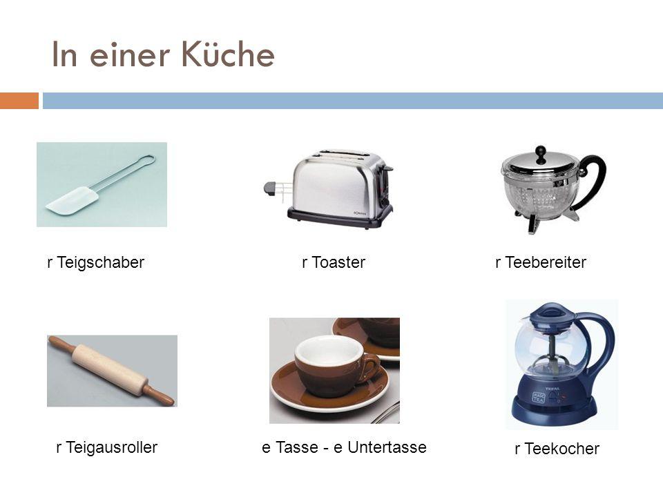 In einer Küche r Teigschaberr Toasterr Teebereiter r Teigausrollere Tasse - e Untertasse r Teekocher