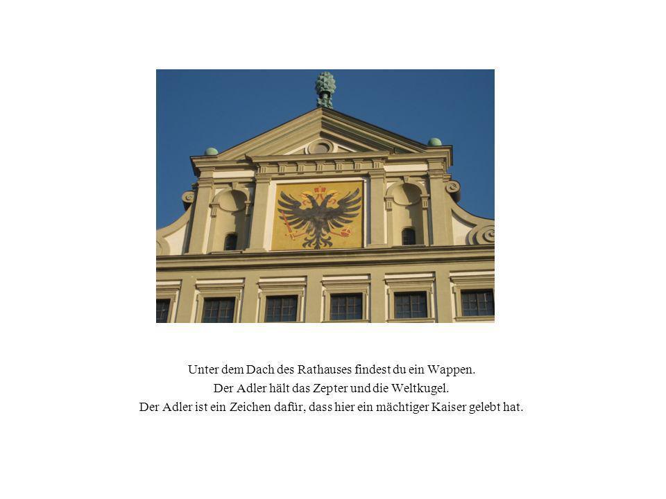 Unter dem Dach des Rathauses findest du ein Wappen. Der Adler hält das Zepter und die Weltkugel. Der Adler ist ein Zeichen dafür, dass hier ein mächti
