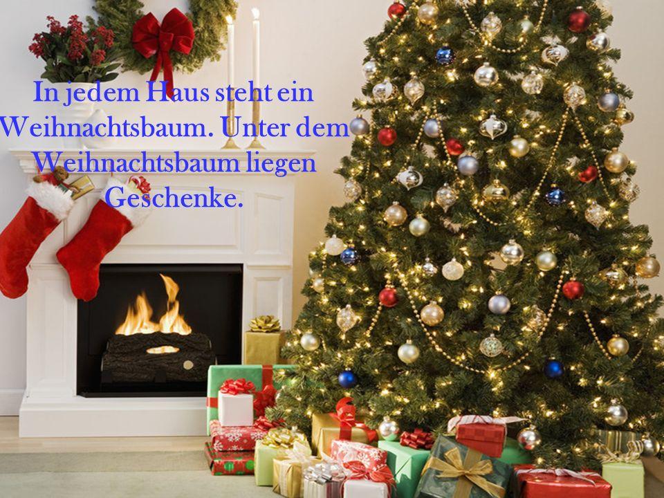 In jedem Haus steht ein Weihnachtsbaum. Unter dem Weihnachtsbaum liegen Geschenke.