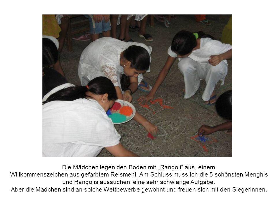 Die Mädchen legen den Boden mit Rangoli aus, einem Willkommenszeichen aus gefärbtem Reismehl.