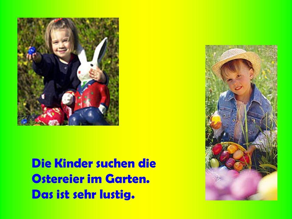 Die Kinder suchen die Ostereier im Garten. Das ist sehr lustig.