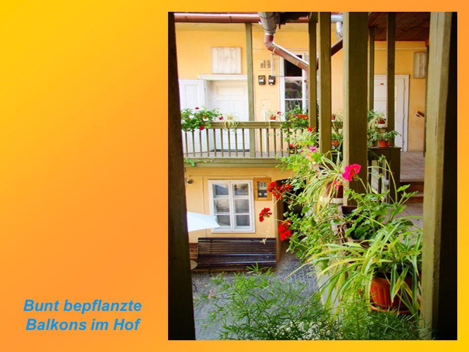 Bunt bepflanzte Balkons im Hof