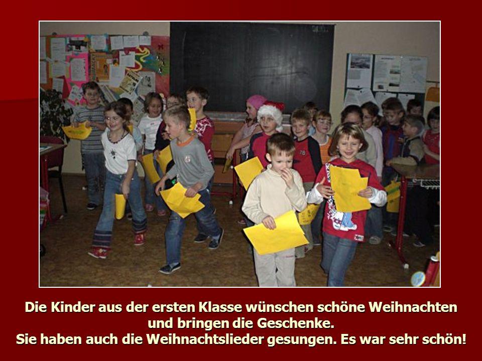 Die Kinder aus der ersten Klasse wünschen schöne Weihnachten und bringen die Geschenke.