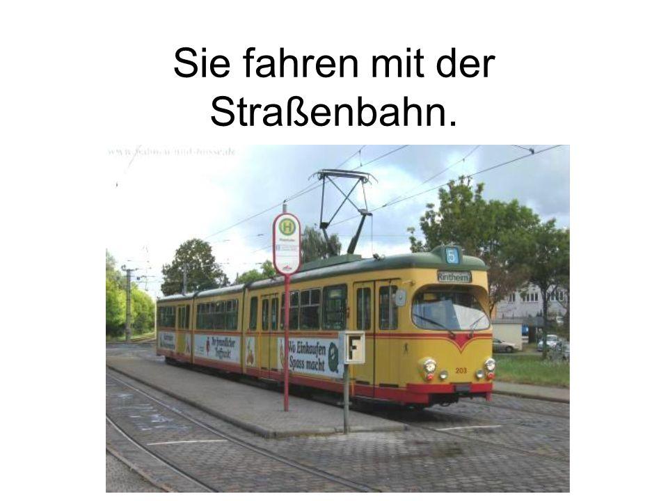Sie fahren mit der Straßenbahn.
