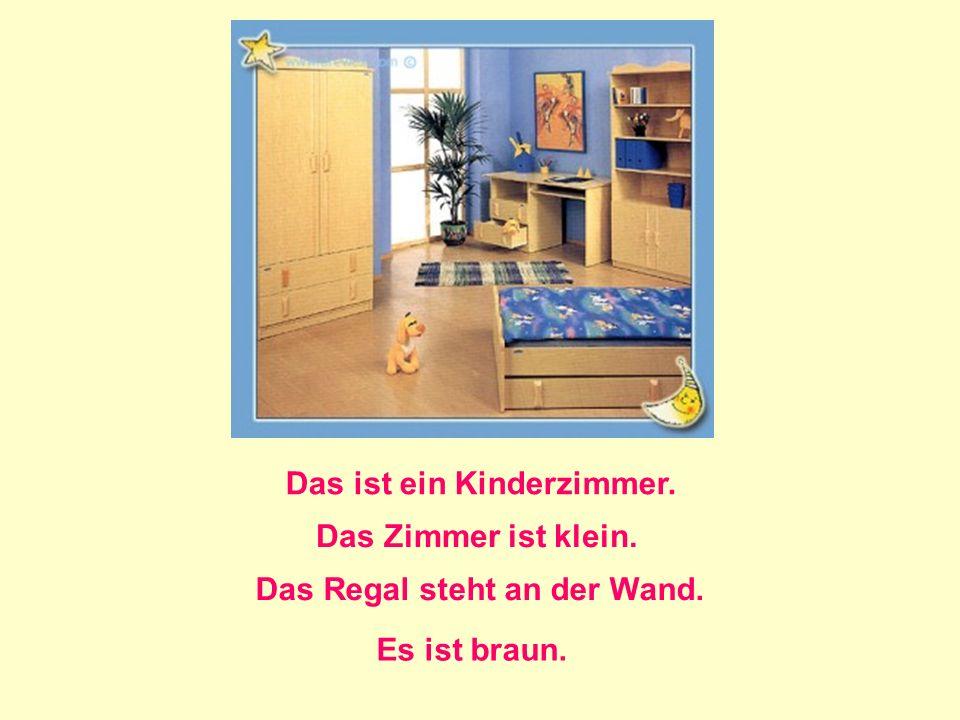 Das ist ein Kinderzimmer. Das Zimmer ist klein. Das Regal steht an der Wand. Es ist braun.